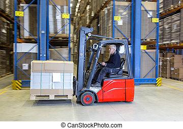 Forklift driving alongside a storage rack. - Man is driving...