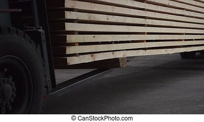 forklift loaders carry large pile of light wooden boards at production plant on sunny day close view slow motion