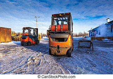 Forklift loaders for warehouse are waiting work outdoors during frosty day in the cargo center. Pallet stacker trucks in winter.