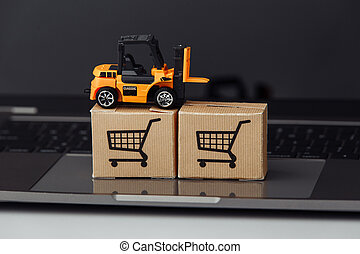Forklift model on carton boxes on a laptop. Courier services concept