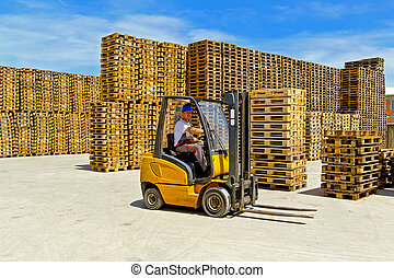 Forklift operator in pallet warehouse on the open
