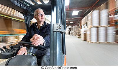 Forklift ride - Elderly man driving a forklift trough a...
