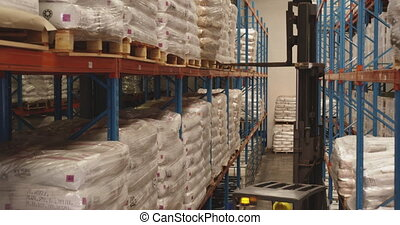 Forklift truck being used in a storage bay at a warehouse 4k