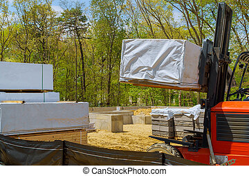Forklift truck driver in an industrial area built home under construction