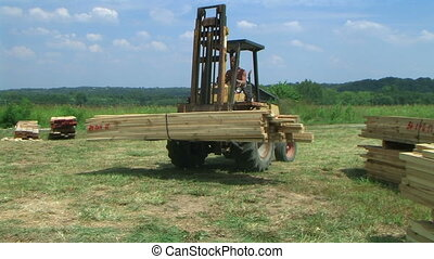 Forklift Unloading Construction Lumber - Forklift unloading...