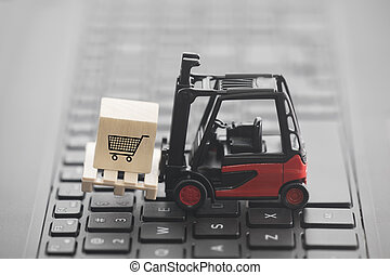 Forklift with shopping cart graphic on wooden block over laptop keyboard