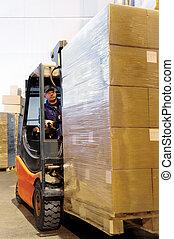 forklift worker in loader at warehouse