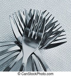 forks - closeup of a pile of forks on a set table with a...