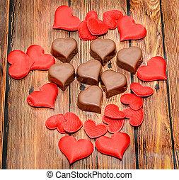 forma corazón, chocolate, con, rojo, corazones, día de valentines, dulces, marrón, madera, fondo.
