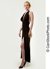 Full body of an attractive woman with hair in bun wearing a long formal black gown with slit showing leg