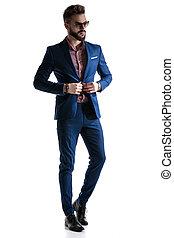 formal businessman in blue suit fixing coat