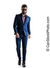 formal businessman in blue suit walking confident