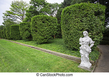 Formal garden with trimmed hedge and a marble statue of woman