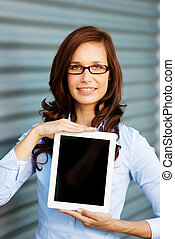 Formal woman - Smiling woman in formal wear showing her ipad...