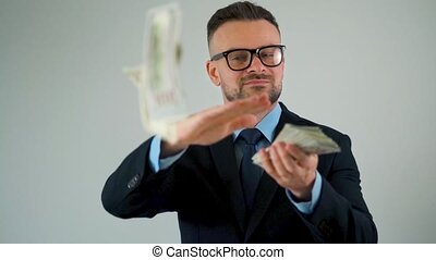 Formally dressed man scatters dollar bills around him, making money rain
