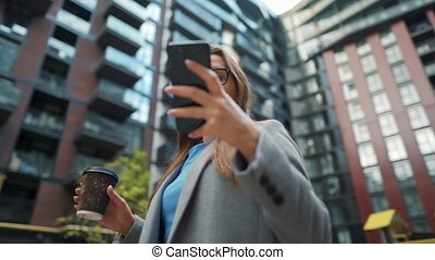 Formally dressed woman standing in a business district with coffee in hand and using a smartphone. Camera moves around her