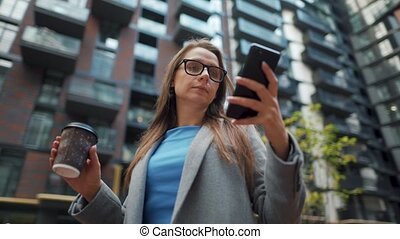 Formally dressed woman standing in a business district with thermo cup in hand and using a smartphone. Camera moves around her