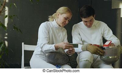 formation, femme, escrimeurs, regarder, escrime, partage, après, deux, concurrence, jeune, intérieur, expérience, smartphone, homme
