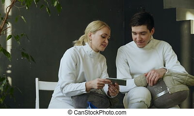 formation, femme, escrimeurs, regarder, escrime, partage, après, deux, expérience, jeune, intérieur, smartphone, travaux pratiques, homme