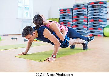 formation, femme, pousées, crise, weight., gymnase, dos, bras, propre, teamwork., utilisation, sport, homme