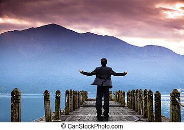 forretningsmand, stand, på, den, kajen, og, iagttag, den, bjerg, og, sky, i, solopgang