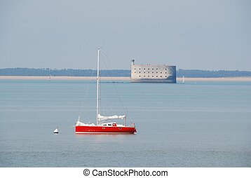 fort boyard and a red sporty sail boat