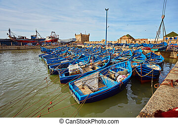 Fort of Essaouira in Morocco on a sunny day with blue boats on the water