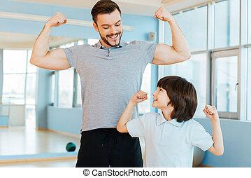 forte, e, healthy., feliz, pai filho, mostrando, seu, bíceps, e, sorrindo, enquanto, ambos, ficar, em, clube saúde