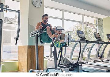 forte, pai, exercitar, ligado, simulador, em, ginásio, mantendo, pequeno, filho, com, seu, legs.