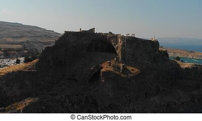 fortress silhouette on brown rocky cliff top lit by sunlight...