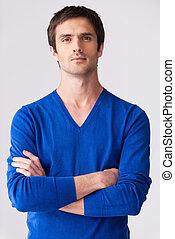 fortuitement, handsome., confiant, jeune homme, dans, bleu, chandail, regarder appareil-photo, et, garder, bras croisés, quoique, debout, contre, gris, fond