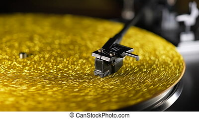 Fortuna gold, movie of retro-styled record player spinning vinyl golden record. Cinemagraph. Side view. Analog audio equipment, sound concept. High quality 4k footage