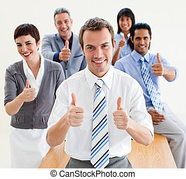 Fortunate business people with thumbs up in front of the camera