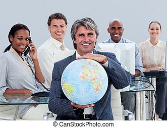 Fortunate business team at work showing a terrestrial globe in the office