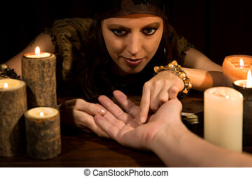 Fortune Teller is reading the lifeline and heart line,...