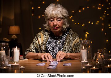 Fortune teller reading tarot cards to predict fate