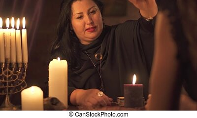 Fortune teller woman in dark room with lots of candles Gives an explaination of future and prediction of fate to a customer using golden wedding ring. 4k UHD