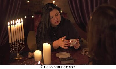 Fortune teller woman in dark room with lots of candles Gives an explaination of future and prediction of fate to a customer with coffee cup thick sediment