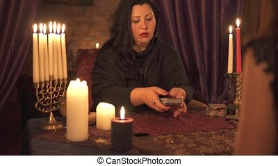 Fortune teller woman in dark room with lots of candles guesses on a tarot card deck. 4k UHD