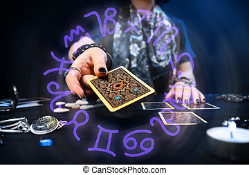 Fortune-telling on cards. The fortune teller hands over a Tarot card. The zodiac circle surrounds the hand. The concept of divination, astrology and esotericism