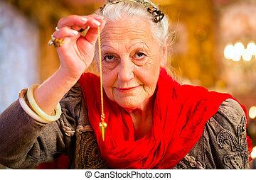 Fortuneteller in Seance with pendulum - Fortuneteller...