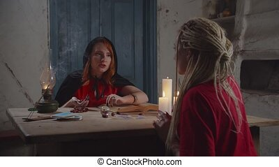 Concentrated charming female fortuneteller in black cape casting magic runes on rustic table, predicting and interpreting the future with spellbook to worried woman during divination in rural house.
