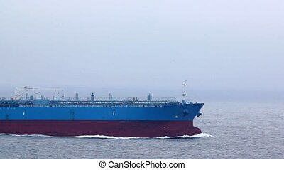 forward part of tanker floating on waves in cloudy weather