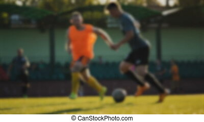 Forward runs and passes the ball, amateur soccer game at the...