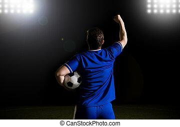 Forward soccer player celebrating after scoring