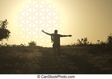 Man running toward the setting sun in the form of flower of life