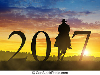 Forward to the New Year 2017 - Silhouette of a cowboy riding...