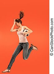 Forward to the victory. The young woman as soccer football player jumping and kicking the ball at studio on a red