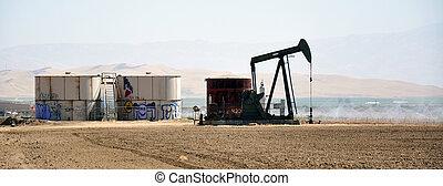 Opertating oil well in near a fruit garden market.