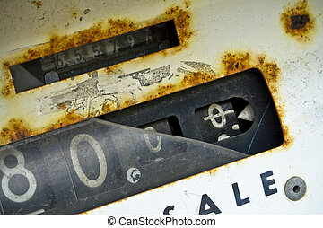 Broken, rusted dial on an obsolete service station gas pump.